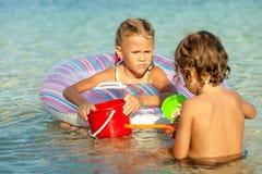 Kleiner Junge und Mädchen, die auf dem Strand zur Tageszeit spielt Lizenzfreies Stockbild