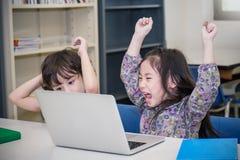 Kleiner Junge und Mädchen, die Computerspiele spielt Stockfotografie