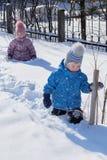 Kleiner Junge und Mädchen, die in den tiefen weißen Schnee geht Stockfotografie