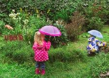 Kleiner Junge und Mädchen, die im Garten unter den Regen bearbeitet Stockbilder