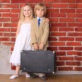 Kleiner Junge und Mädchen, die mit einem Koffer steht Lizenzfreie Stockbilder