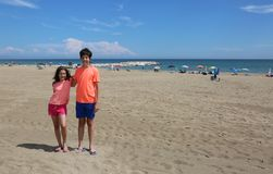 Kleiner Junge und Mädchen, die am Strand sich umarmt Stockfotografie
