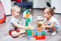 kleiner Junge und Mädchen, die zu Hause Spielwaren spielt stockfotos