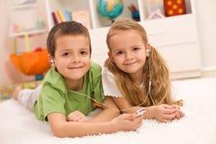 Kleiner Junge und Mädchen, die zusammen Musik hört stockfotos