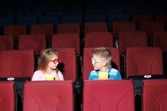 Kleiner Junge und Mädchen in farbigen Gläsern mit Popcorn Lizenzfreies Stockfoto