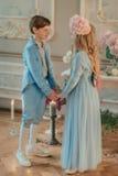Kleiner Junge und Mädchen im blauen Kleid im Studio mit Blumen Stockfotos