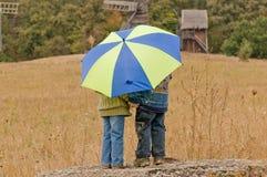 Kleiner Junge und Mädchen mit Regenschirm Stockfotografie