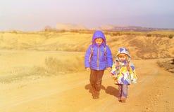 Kleiner Junge und Mädchen mit Rucksäcken reisen auf die Straße Stockbild