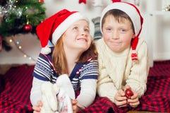 kleiner Junge und Mädchen nahe Weihnachtsbaum Stockfotos