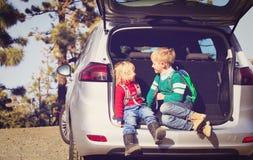 Kleiner Junge und Mädchen reisen mit dem Auto auf Straße in der Natur Lizenzfreie Stockfotografie