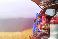 Kleiner Junge und Mädchen reisen mit dem Auto in Berge Stockfotografie