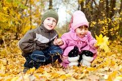 Kleiner Junge und Mädchen spielen in einem Park im Herbst Stockfotografie