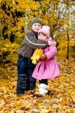 Kleiner Junge und Mädchen spielen in einem Park im Herbst Lizenzfreies Stockbild