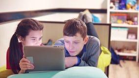 Kleiner Junge und Mädchen spielen und Hund auf der Tablette, die auf dem Bett liegt Internet des Jungen- und Mädchenteenagersocia stock video
