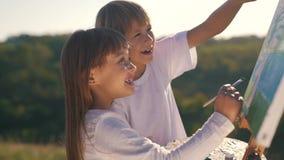Kleiner Junge und Mädchen zeichnen das Bild stock footage