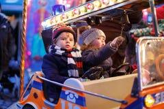 Kleiner Junge und Mädchen auf einem Karussell am Weihnachtsmarkt Lizenzfreies Stockfoto