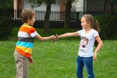 Kleiner Junge und Mädchen, die Hände im Park, im Freien rüttelt Stockfoto