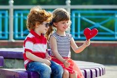 Kleiner Junge und Mädchen mit Herzen Stockfotos