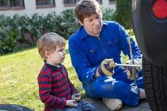 Kleiner Junge und sein änderndes Rad des Vaters auf Auto Lizenzfreie Stockbilder