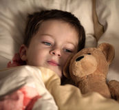 Kleiner Junge und sein Teddybär werden schlafen Lizenzfreies Stockbild