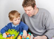 Kleiner Junge und sein Vater, die über selbst gemachte Ostereier glücklich ist Stockbild