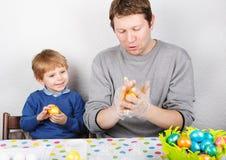 Kleiner Junge und sein Vater, die über selbst gemachte Ostereier glücklich ist Lizenzfreie Stockbilder