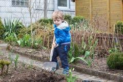 Kleiner Junge und sein Vater, die Samen im Gemüsegarten pflanzt Lizenzfreie Stockfotos