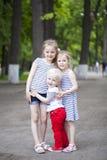 Kleiner Junge und zwei ältere Vetter, treffend im Sommerpark Lizenzfreie Stockfotos