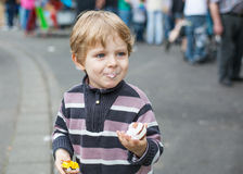 Kleiner Junge von drei Jahren essend an einem Funfair, draußen lizenzfreies stockfoto