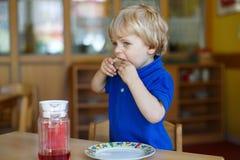 Kleiner Junge von zwei Jahren, die an der Kindertagesstätte frühstücken Lizenzfreie Stockfotografie