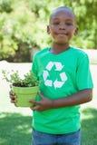 Kleiner Junge, wenn das T-Shirt aufbereitet wird, das Topfpflanze hält lizenzfreie stockbilder