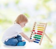Kleiner Junge zählt auf dem Abakus lizenzfreie stockbilder
