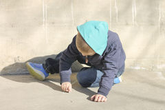 Kleiner Junge zeichnet auf Asphalt Stockbild