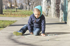 Kleiner Junge zeichnet auf Asphalt Stockbilder