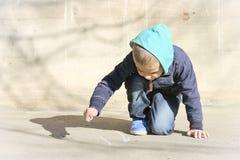 Kleiner Junge zeichnet auf Asphalt Stockfoto