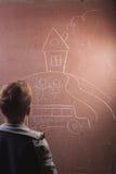 Kleiner Junge zeichnet mit Kreide auf einer Tafel, Lizenzfreie Stockbilder