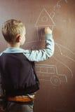 Kleiner Junge zeichnet mit Kreide auf einer Tafel, Stockbild