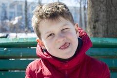 Kleiner Junge zeigt seine Zunge und macht Gesicht Lizenzfreies Stockbild