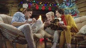 Kleiner Junge zeigt seinem älteren Bruder und Mutter auf Heiliger Nacht Smartphoneschirm stock video footage