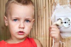 Kleiner Junge zieht das Netzkabel stockfotografie