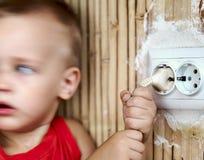 Kleiner Junge zieht das Netzkabel lizenzfreie stockbilder