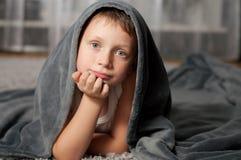 Kleiner Junge zu Hause auf dem Teppich Lizenzfreie Stockfotografie