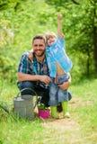kleiner Jungenkinderhilfsvater bei der Landwirtschaft Gie?kanne, Topf und Hacke Gartenger?te Gl?cklicher Tag der Erde Leere Felde lizenzfreie stockfotos
