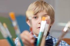 Kleiner Künstler, der hinter Malerpinseln sich versteckt Lizenzfreies Stockfoto