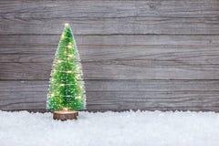 Kleiner künstlicher grüner Weihnachtsbaum mit Lichterkette auf sno Lizenzfreies Stockfoto