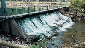 Kleiner künstlicher Wasserfall, mit einer Fußgängerbrücke stock video footage