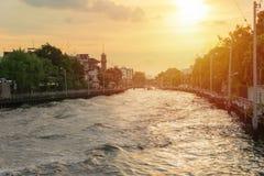Kleiner Kanal und alte Fähre mit Sonnenuntergang stockbild