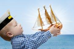 Kleiner Kapitän mit dem Schiff Stockbilder
