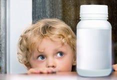 Kleiner kaukasischer blonder Junge musterte, die weiße Flasche betrachtend Stockfoto