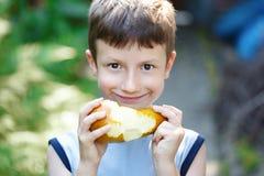 Kleiner kaukasischer Junge, der die Birne im Freien isst Stockfotografie